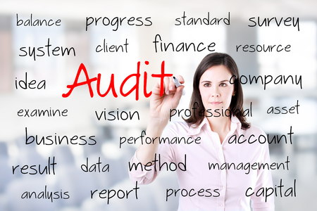 Young business woman writing audit concept. Office background.