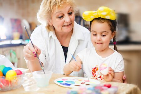 Photo pour Grandmother with granddaughter are coloring eggs for Easter. white, t-shirt, brushes - image libre de droit