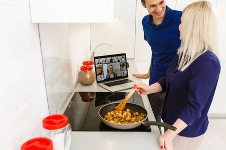Photo for Young woman cooks in front open laptop and videochating in the kitchen - Royalty Free Image