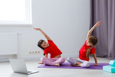 Photo for two little girls practicing yoga, stretching, fitness by video on notebook. Distant online education training, aerobic at home. Healthy lifestyle, coronavirus, stay home. Kids sport home quarantine. - Royalty Free Image