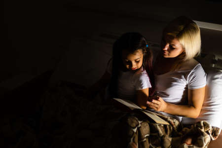 Photo pour Mother And Daughter Learning To Read At Home - image libre de droit