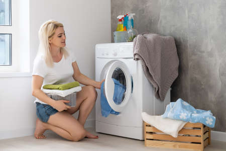 Photo pour pretty smiling girl in the laundry room - image libre de droit