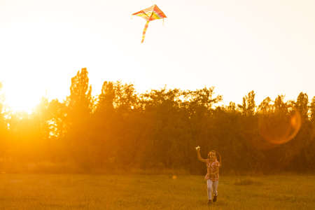 Photo for Two kids flies a kite over sunset in park - Royalty Free Image
