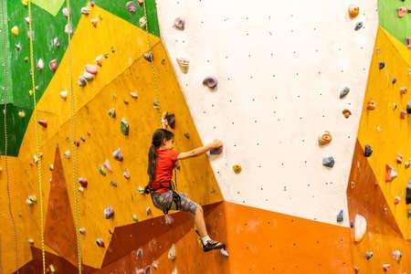 Photo pour Sporty little girl climbing artificial boulder on practical wall in gym - image libre de droit