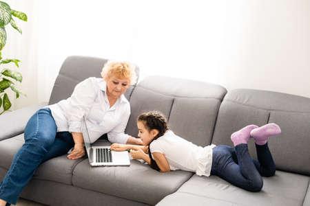 Photo pour modern grandmother teaching grandchild how to use laptop computer at home - image libre de droit