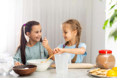 Photo for two little girls prepare Christmas cookies in the kitchen - Royalty Free Image