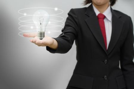 Business woman holding idea lamp