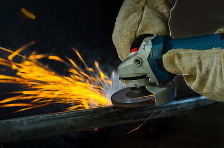 Close up iron worker cutting metal