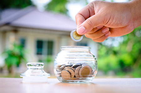 Male hand putting money coins with home, Saving for buy home concept