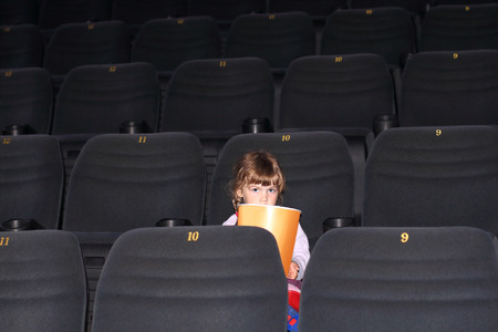 Little girl with two braids with big portion of popcorn sitting in cinema hall