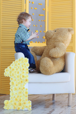 Little handsome happy boy stands on soft armchair and plays with big bear toy