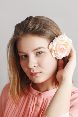 Cute girl teenager in pink dress poses with white rose in hair in studio