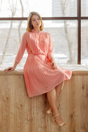 Girl teenager in pink dress sits soft window sill in studio, full body