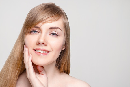 Photo pour Happy young woman with make-up touches her cheek in studio, close up portrait - image libre de droit