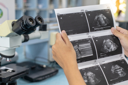 Photo for Doctor reading ultrasound results of a pregnant woman. - Royalty Free Image
