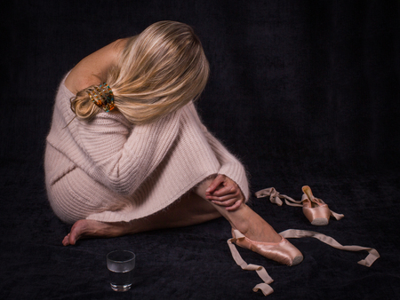 Wearied ballerina  with an inclined head, dressed in a warm pink sweater,  sits on the floor with loose ballet shoes, glass of water, on the black background.