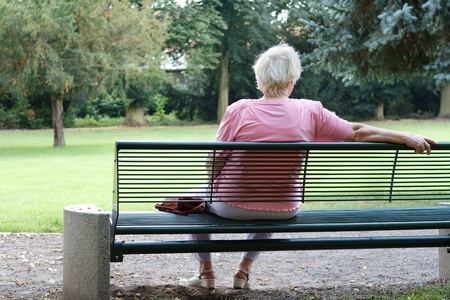 Senior woman is sitting alone in a park