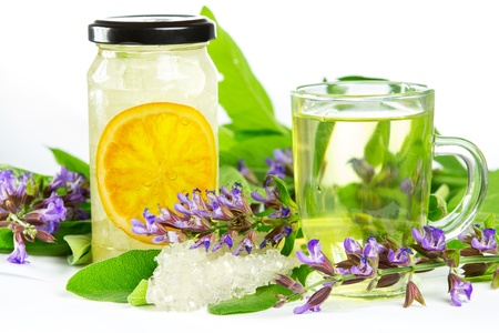 Glass of sweet herbal tea with flowering salvia and sage, sugar crystals and sliced orange, a medicinal remedy used in Auyurveda naturopathy