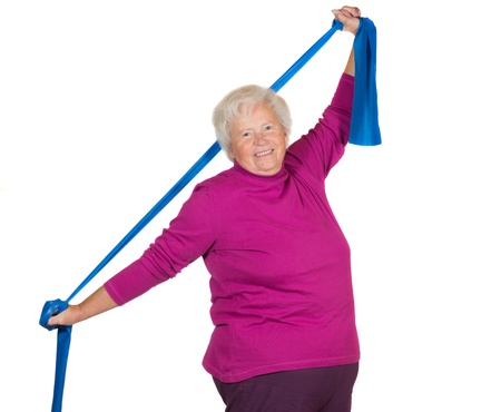 Happy overweight senior lady exercising stretching her arms above her head using a strap to improve her flexibility and strengthen her neck and shoulder musclesの写真素材