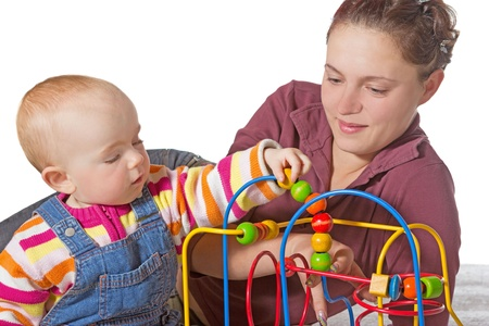 Baby with motor activity development delay being stimulated to develop muscle coordination and movement on a bead maze watched by a devoted mother