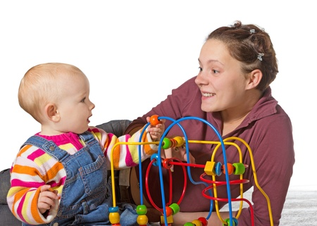 Baby with motor activity development delay being stimulated to develop coordination and muscle control and movement on a bead maze by an adoring mother