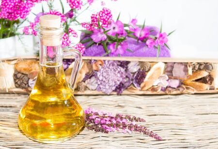 Essential oil for bath and wellness, with fresh flowers.