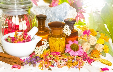 Naturopathy and aromatherapy still life with a pestle and mortar alongside fresh and dried flowers, floral potpourri and essential oil extracts in bottles and celestine for crystal healing