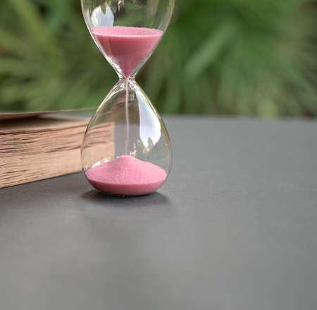 Photo pour Hour glass with sand flowing,  next to a book. Close up. Time management concept. - image libre de droit