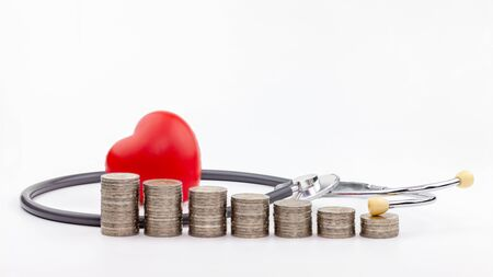 coins, stethoscope and red heart on white background,Saving money for Medical expenses and Health care concept