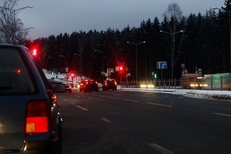Winter, a lot of snow, cold. Back view. brake lights are on the car. Red light on a setafor. Evening, dark, bad, seeing the road