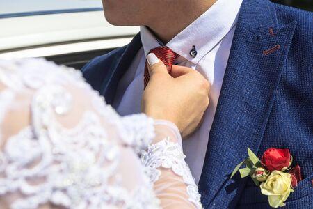 Foto de daylight. Bride straightens the groom's red tie. have toning. - Imagen libre de derechos