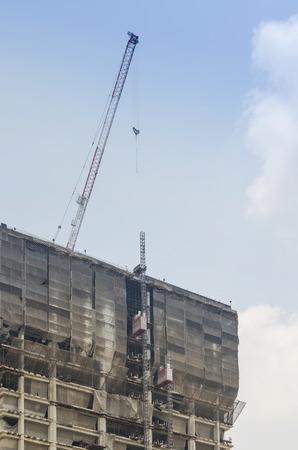 Photo pour Building and crane under construction against blue sky - image libre de droit