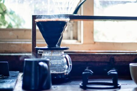 Photo pour Vapor coming out of a coffee cup and brewing fresh coffee in the background - image libre de droit