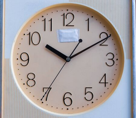 analog clock pointing hour hand at 10, minutes hand at 2 and seconds hand at 7. selective focus