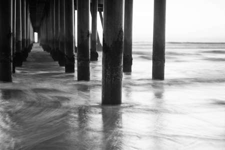 A shot looking out under a pier at all the columns during sunset.