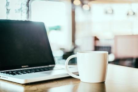 Photo pour Coffee cup, laptop in coffee shop - image libre de droit