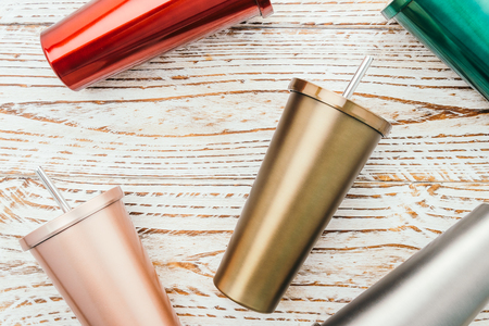 Stainless and tumbler cup on wooden background