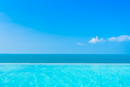 Photo for Beautiful landscape of sea ocean with outdoor swimming pool on white cloud blue sky background for leisure travel and vacation - Royalty Free Image