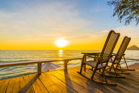 Photo for Empty wood chair and table at outdoor patio with beautiful tropical beach and sea at sunrise or sunset background for vacation and travel - Royalty Free Image