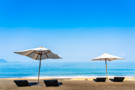 Chair umbrella and lounge on the beautiful beach sea ocean on sky for leisure travel and vacation concept