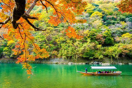Photo pour Beautiful Arashiyama river with maple leaf tree and boat around lake in Autumn season Kyoto Japan - image libre de droit