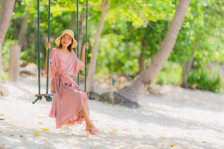 Photo pour Portrait young asian woman sitting on swing rope and sea around beach sea ocean coconut palm tree for travel in holiday vacation concept - image libre de droit