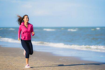 Foto de Portrait beautiful young asian woman running and exercising on the tropical outdoor nature beach sea ocean for healthy - Imagen libre de derechos