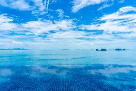 Photo for Beautiful outdoor swimming pool with sea ocean on white cloud blue sky background for holiday vacation travel concept - Royalty Free Image