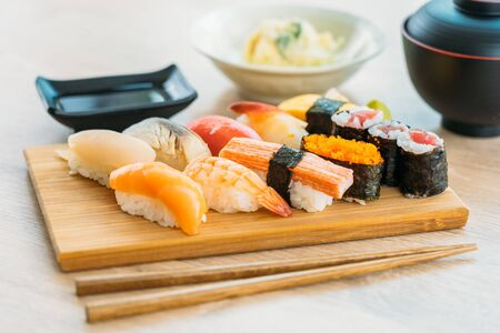 Foto per Salmon tuna shell shrimp and other meat sushi maki on wood tray with sauce and soup - Japanese food style - Immagine Royalty Free