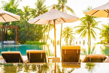 Photo pour Beautiful outdoor tropical nature landscape of swimming pool in hotel resort with coconut palm tree umbrella and chair nearly sea ocean beach at sunrise time - image libre de droit