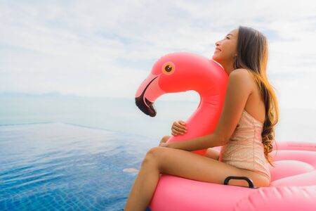 Photo pour Portrait young asian woman on inflatable float flamingo around outdoor swimming pool in hotel resort for holiday vacation concept - image libre de droit