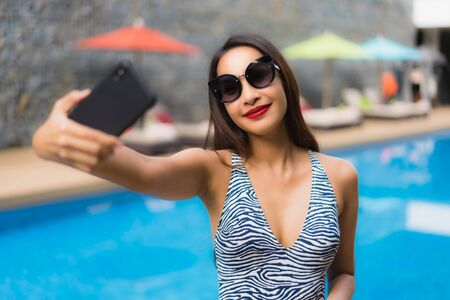 Photo pour Portrait beautiful asian woman using mobile phone around outdoor swimming pool in holiday vacation - image libre de droit