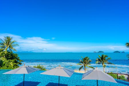 Photo for Beautiful luxury outdoor swimming pool in hotel resort with sea ocean around coconut palm tree and white cloud on blue sky for holiday vacation travel - Royalty Free Image