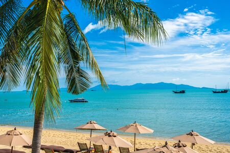 Photo pour Beautiful tropical beach sea and ocean with coconut palm tree  and umbrella and chair on blue sky and white cloud for holiday vacation travel - image libre de droit